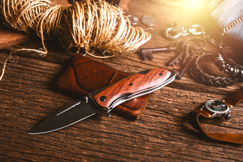 Lube oiled folding hunting knife with wooden handle