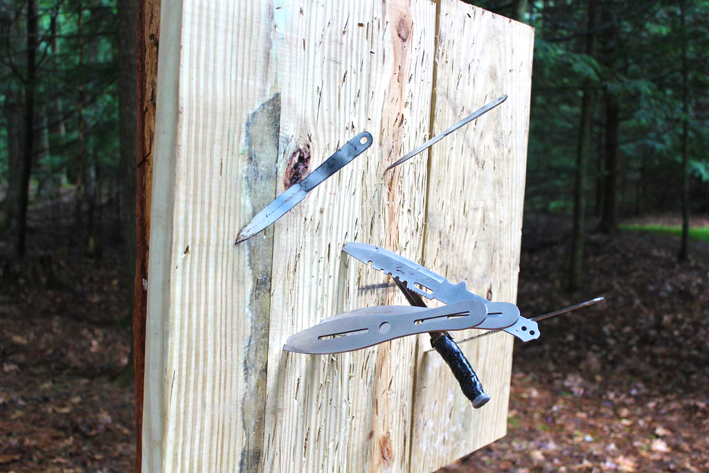 Wooden throwing target with bunch of throwing knives